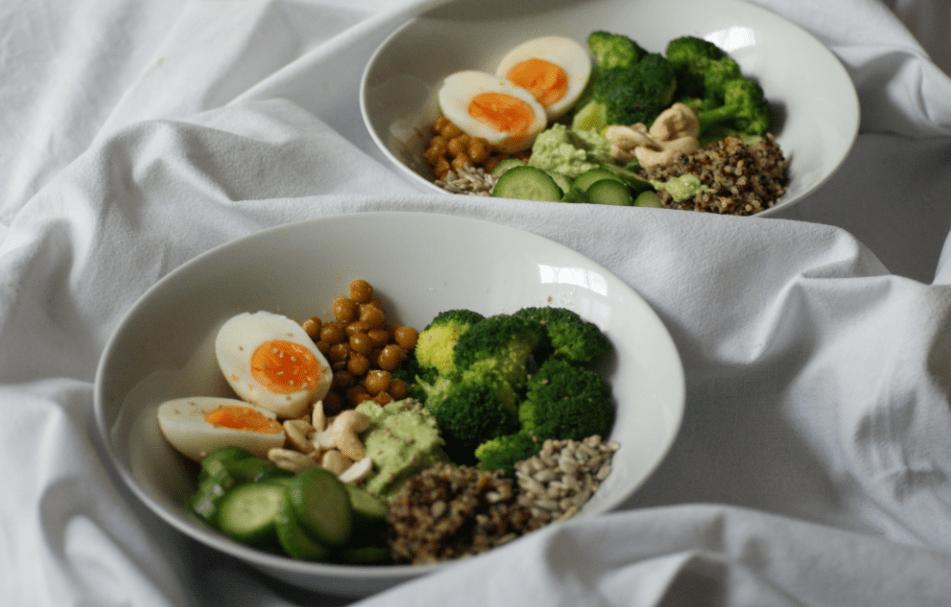 Buddha Bowl mit Kichererbsen, Eiern, Avocado, Brokkoli, Quinoa, Cashew und Gurken